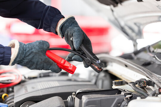 Human trying to start engine with jumper cables in close up