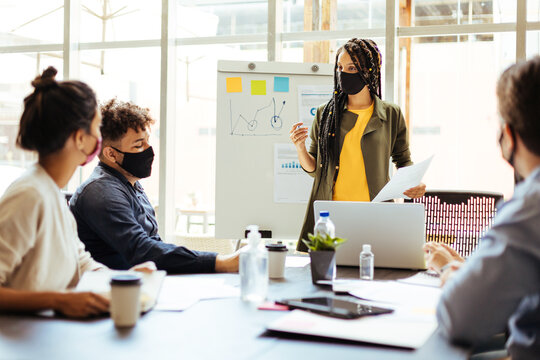 Business team wearing protective masks while meeting in the office during the COVID-19 epidemic. Woman presenting project to colleagues