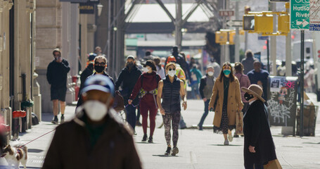 Anonymous crowd of people walking street wearing masks during Covid 19 pandemic in New York City