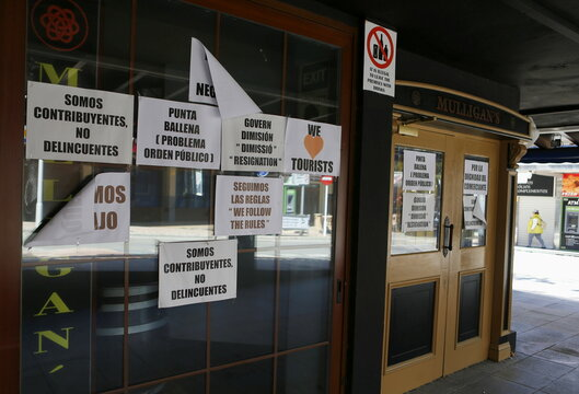 Signs with messages against the local government's pandemic measures and encouraging tourists to visit are seen on the doors of a closed bar, at Punta Ballena street
