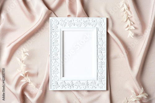 Elegant vintage photo frame mockup on silk background. Flat lay, top view, copy space. Wedding, Mothers Day greeting card template.