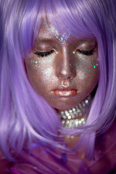 A little girl in a purple wig with silver sequins on her face. An alien, fantasy world.A fairy or an alien. Eyes closed. A peaceful face, calm.