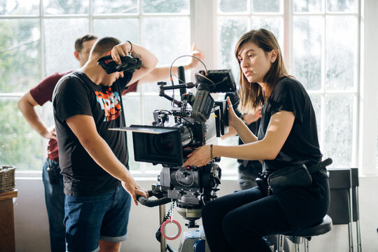 Female director of photography with a camera on a movie set. Professional videographer on the set of a movie