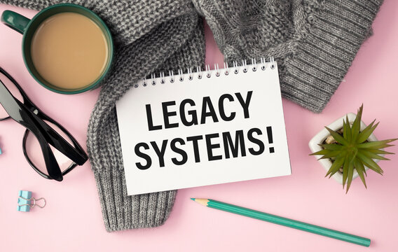 LEGACY SYSTEMS is written in a white notepad near a calculator, coffee, glasses and a pen. Business concept