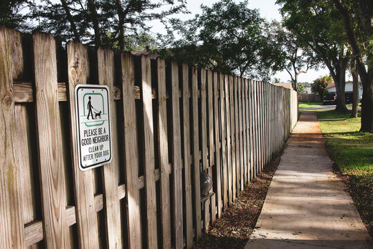 Pick Up After Your Dog Sign on a Fence