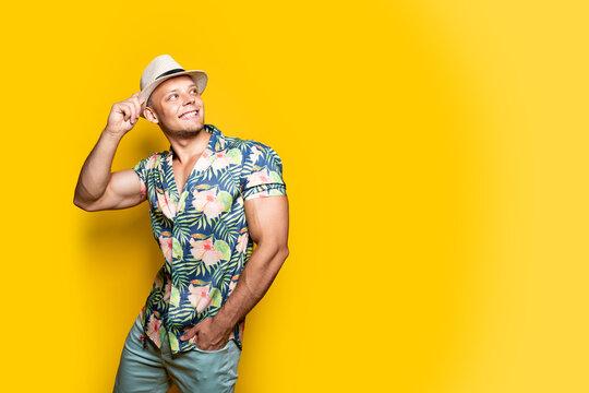 Young handsome Caucasian man wearing Hawaiian shirt, hat posing against yellow wall in studio