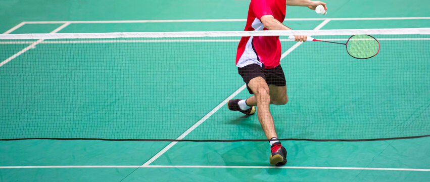 Professional badminton player beats the shuttlecock in the arena