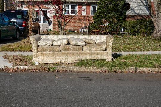 Old worn out couch by the curb waiting for trash pickup in front of an old house with a messy yard