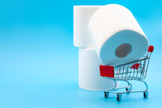 Mass hysteria and panic buying concept with toilet paper and shopping cart isolated on blue background with copy space