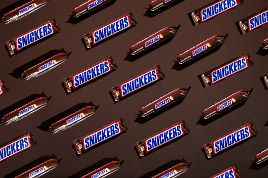 Kiev, Ukraine - March 25, 2021: Snickers chocolate bars on brown background. Modern composition