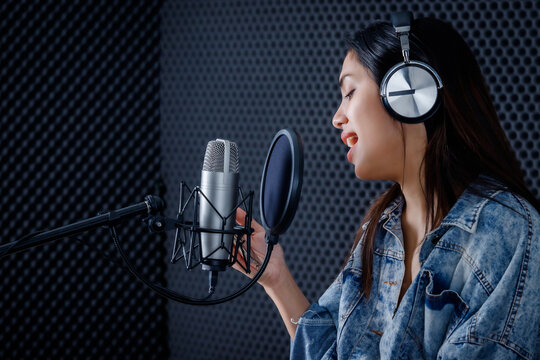 Happy cheerful pretty smiling of portrait of young Asian woman look at the smartphone vocalist Wearing Headphones recording a song front of microphone in a professional studio
