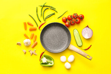 Frying pan and different vegetables on color background