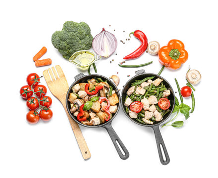Frying pans with tasty vegetables and chicken on white background