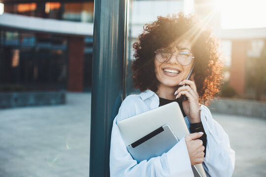 curly haired woman is talking on phone posing outside with a laptop wearing glasses