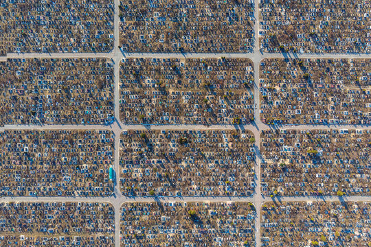 Aerial view of huge urban cemetery with grid layout. Increase in the scale of the cemetery due to the excessive number of deaths by Covid-19 pandemic