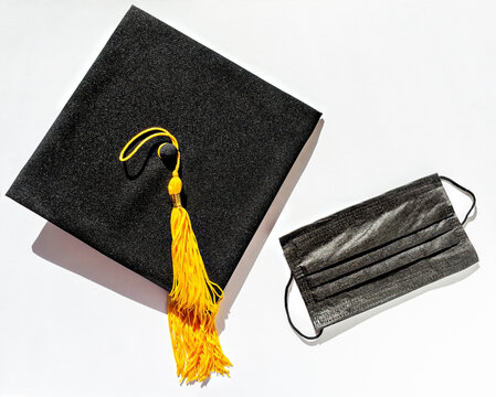 Black graduate cap with yellow tassel and protective face mask on white background, protection from virus while studying, getting diploma in new reality, new normal, Flat lay, top view, mortarboard