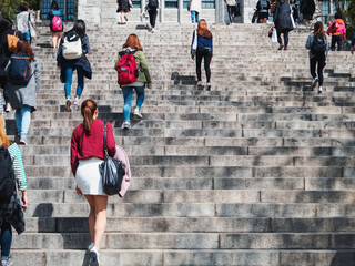 Asian Women walking on stair-step outdoor building Campus life Asian Student