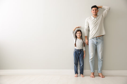 Little girl and father measuring their height near light grey wall indoors. Space for text