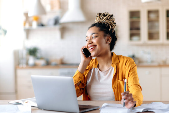African American joyful attractive stylish young woman, freelancer, manager or real estate agent, having pleasant phone conversation with client or employee, sitting at workplace, smiling