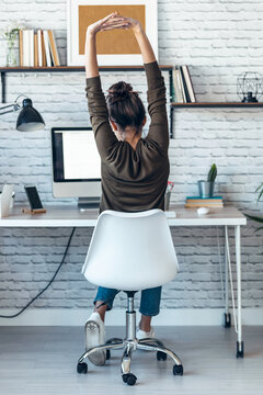 Beautiful businesswoman stretching body for relaxing while working with computer in the office at home.