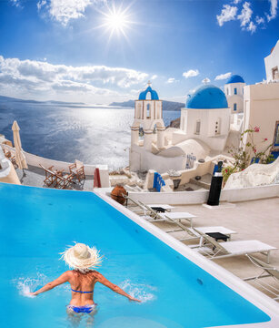 Santorini island with young woman in the swimming pool in Oia village against traditional churches, Greece