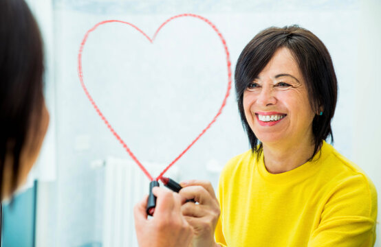Positive senior woman drawing heart shape on the mirror at home - Self love and self care concept