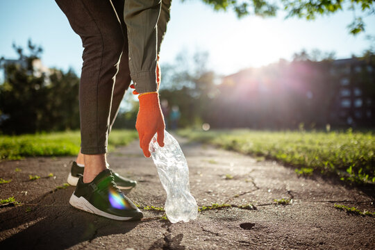 Young man volunteer collects used plastic bottle from the ground outdoors wearing gloves. Volunteer cleans up the park on a sunny bright day. Clearing, pollution, ecology, plastic concept.