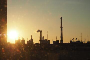 Pomarańczowy zachód słońca nad miastem wśród dachów