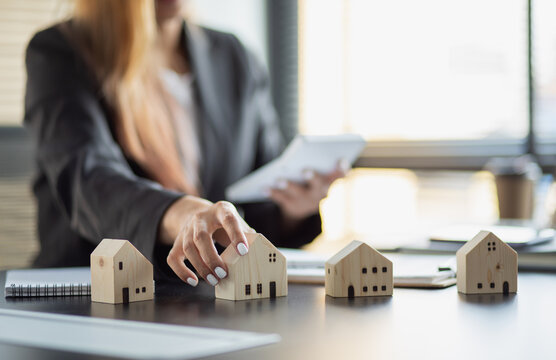 Close up wooden toy house with business woman signs a purchase contract or mortgage for a home, Real estate concept.