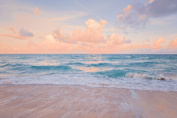 Sea ocean beach sunset sunrise landscape outdoor. Water wave with white foam. Beautiful sunset airy red sky with clouds. Natural aquatic blue pink turquoise aquamarine colorful background.
