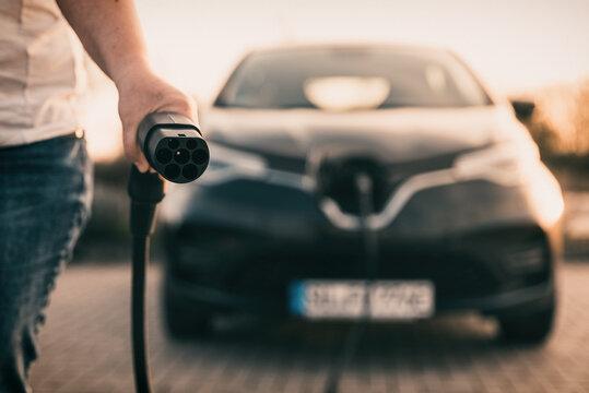 Ladekabel von Elektroauto wird in einer Hand gehalten