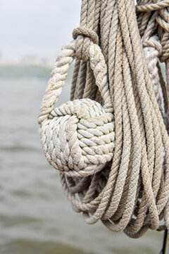A  monkey fist knot tied to the end of a rope to use as a weigh or an anchor. . Closeup. Copy space.