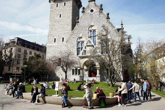 People enjoy sunny spring weather in front of St. Jakob church in Zurich