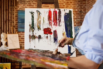 Painter at the studio creating abstract picture on canvas using oil paintings and palette knife. Young female artist working. Creative process, relax,leisure,hobby, stress management