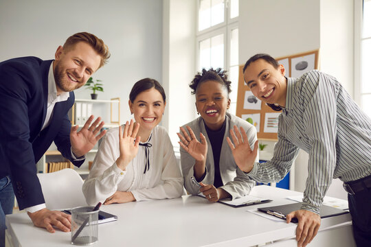 Team of happy young diverse business people sitting and standing around office table, smiling, looking at camera and waving hello, greeting international coworkers in remote work meeting via Internet