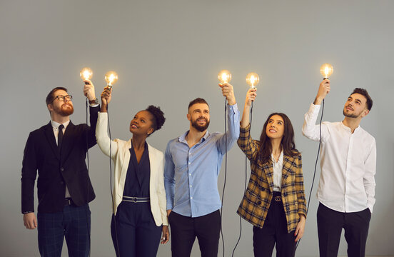 Group of happy creative young diverse business professionals holding glowing light bulbs standing on gray studio background. Innovative thinking, finding solution, people developing own idea concept
