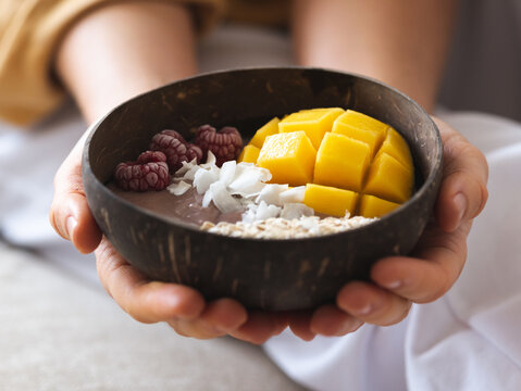 Crop anonymous female holding power bowl with fresh tasty mango and coconut chips in daytime