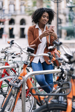 Smiling African American female standing near parked bike and browsing mobile phone in city