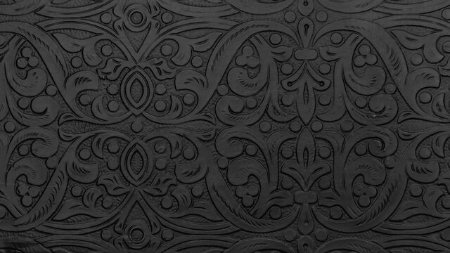 Textured black metal backdrop with ancient oriental floral wavy ornament. Background floral carved silver black, decorative asian religious chasing art.
