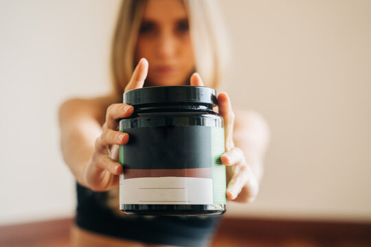 Blurred anonymous female wearing activewear with sports nutrition jar for body building in hands standing in room during training at home