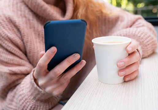 Crop anonymous female in warm sweater sitting at table with cup of hot drink and using mobile phone