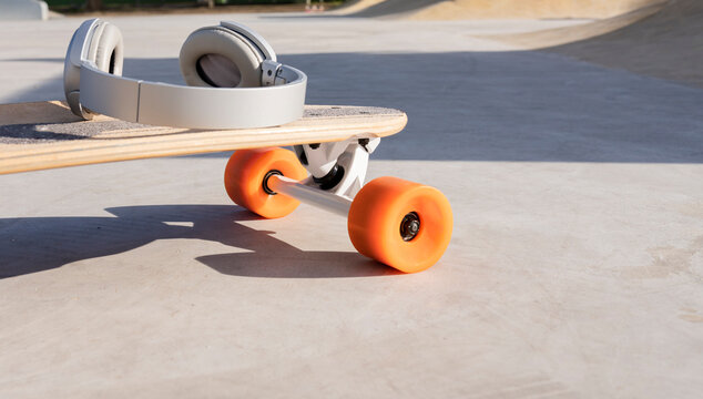 Contemporary wireless headset on longboard with bright wheels in skate park on sunny day