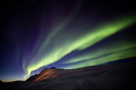 Low angle of spectacular night starry sky with glowing purple and green aurora borealis over mountains covered with snow in winter in Norway