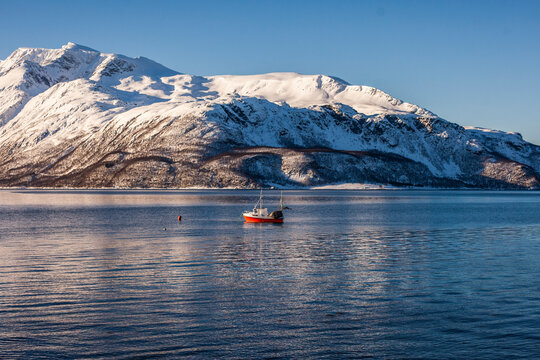Majestic view of fishing boat floating on calm sea water on sunny day on background of snowy mountains in Norway in winter