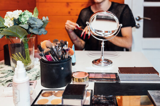Crop unrecognizable transsexual man at table with collection of beauty products and mirror in cabin