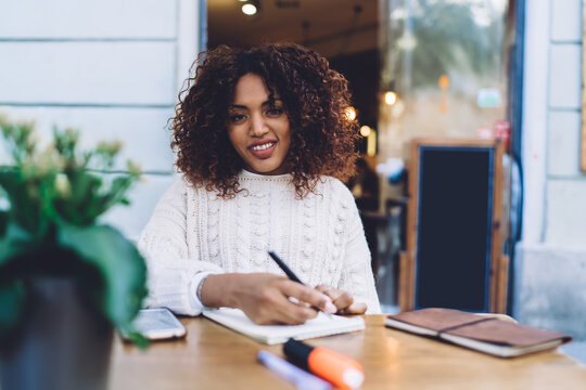 Smiling black woman writing notes in notebook
