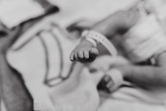Black and white soft focus of crop unrecognizable newborn baby in diaper with tag on leg lying in hospital cradle