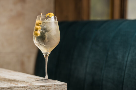 Crystal wineglass with Martini cocktail served with lemon zest and olives edge of wooden table
