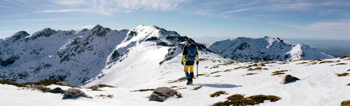 Back view of unrecognizable climber walking on slope of snow covered rocky mountain range in sunny weather