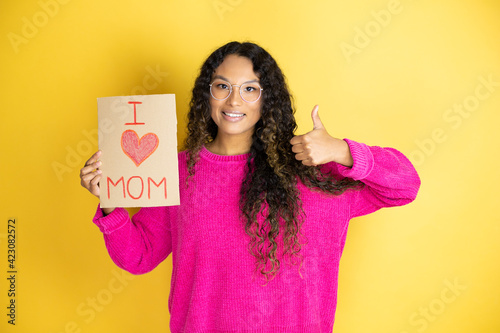 Beautiful woman celebrating mothers day holding poster love mom message doing positive gesture with hand, thumbs up smiling and happy. cheerful expression and winner gesture.